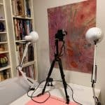 Lights set up to photograph a mini quilt on the wall