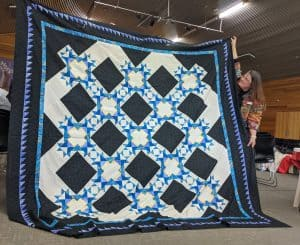 HUGE quilt with blacks and whites and blues and teals.